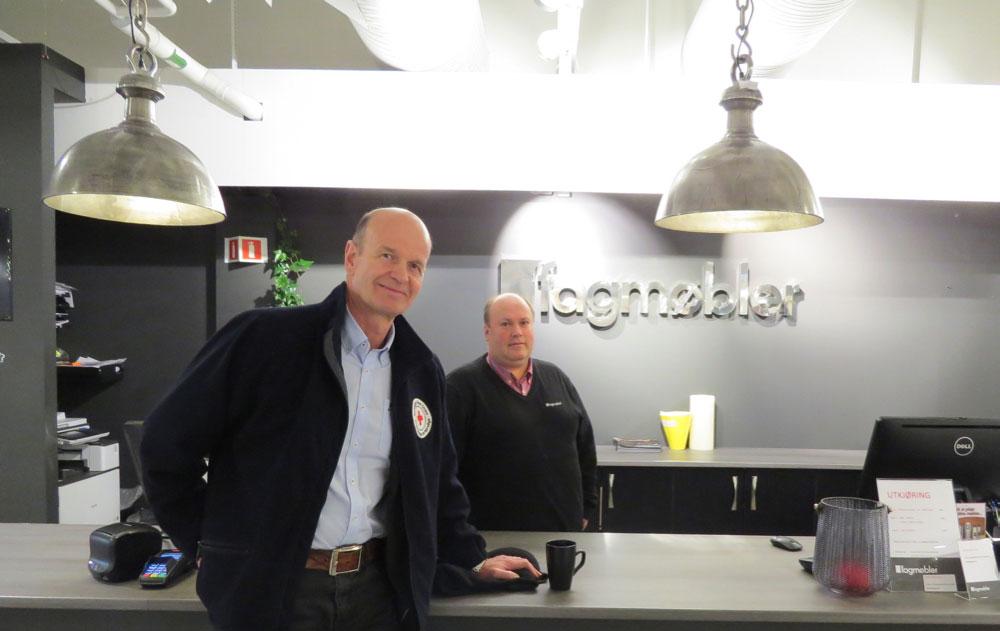 President i Røde Kors Sven Mollekleiv besøker Fagmøbler i Drammen – her representert ved daglig leder Gunnar Sandnes (bak disken), for å takke for bidraget. (Foto: Ann Christin Håland/Røde Kors)