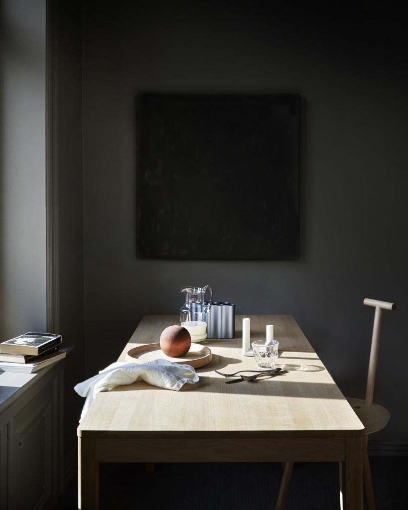 Kjøkkenbord: Naturlig lys er en viktig medspiller i ethvert interiør og fremhever nydelig teksturene i ulike materialer. Kjøkkenbordet i eik er fra Norrgavel, det runde eikefatet fra Skagerak, trekulen fra Cosina, glassmuggen fra Verket Interiør og vasen i metall fra Vitra. Drikkeglasset er fra Frama, lysestaken fra Backe i Grensen, bestikket fra Bo Bedre AS og linservietten fra Norway Designs. Stolen Spade er designet av Faye Toogood for Please Wait to be Seated og er fra Kollekted by.