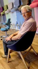 Robert Kalstad på plass i en NOR-stol produsert for Tynes. Bak skimter vi en omtrukket Capisco-stol, og på veggen henger på rekke og rad flere utførelser av damestoler som er polstret opp med spiralfjærer og vatt i sete. (Foto: Odd Henrik Vanebo)